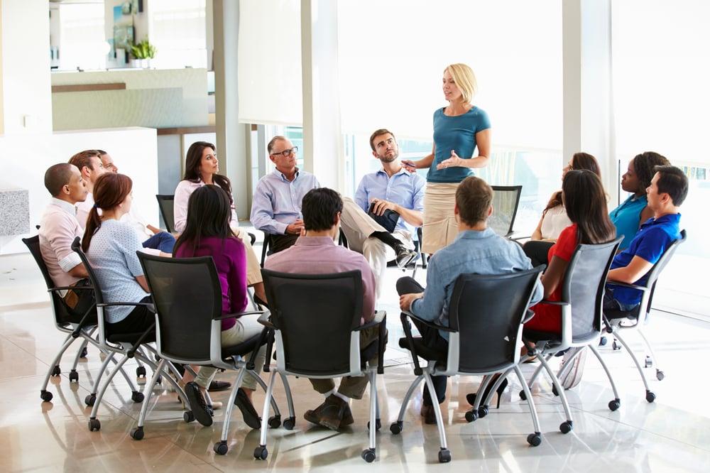 businesswoman-addressing-multi-cultural-office-sta-PKA7GMQ