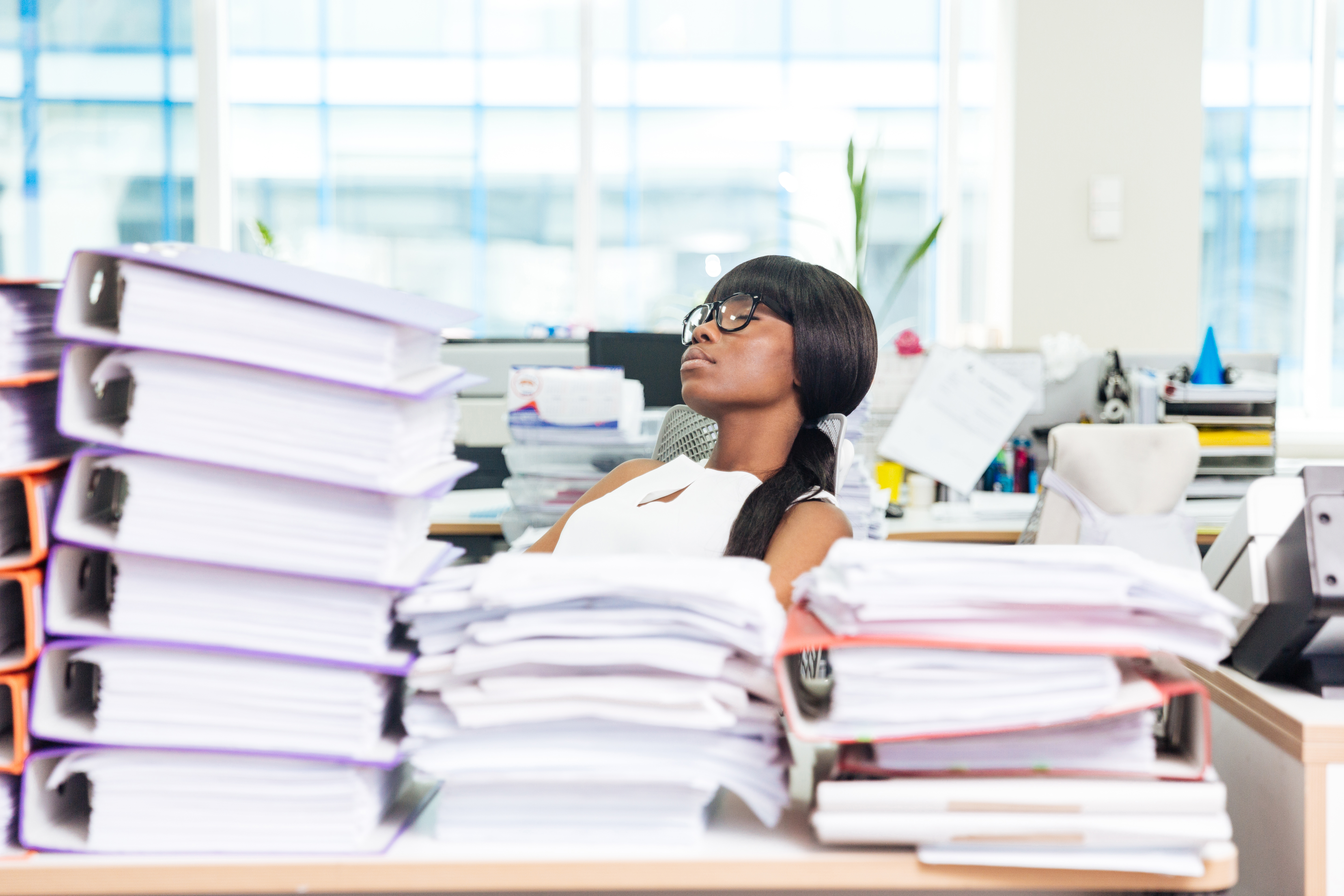 businesswoman-sleeping-in-office-with-many-work-P8JXKTP