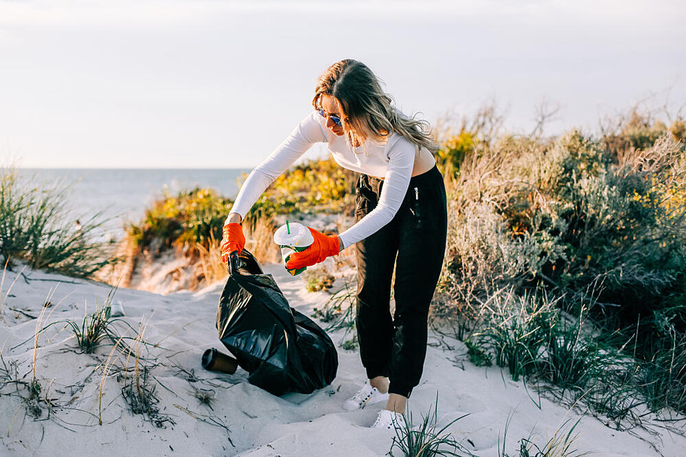 picking-up-trash-picking-up-plastic-waste-in-a-bin-bag-at-the-beach-volunteer-cleaning-beach-beach_t20_drmb1A