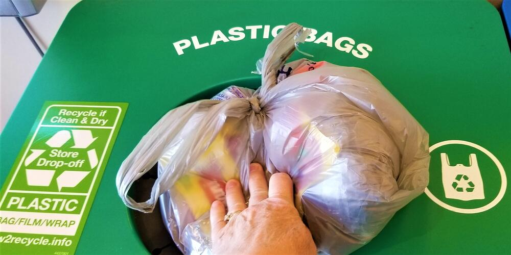recycling-a-person-puts-many-plastic-grocery-bags-shopping-bags-and-other-plastic-wrap-to-be-recycled_t20_QzK6XE
