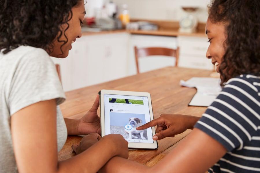 two-teenage-girls-using-social-media-on-digital-ta-PZRN9Y2