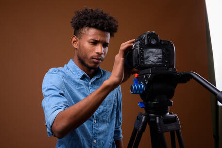 young-handsome-african-man-vlogging-with-dslr-came-9QBL5H8